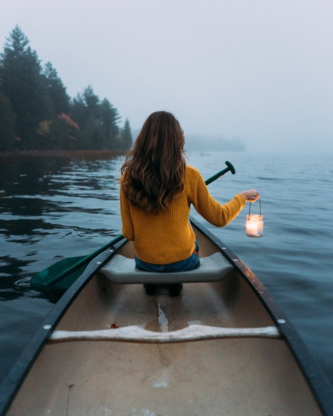 Girl in a canoe with a lantern