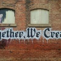 Together we create graffiti on brick wall