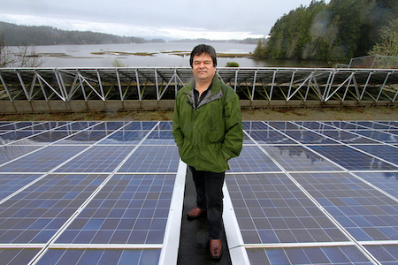 T'Sou-ke Chief Gordon Planes amongst a sea of solar modules on the canoe shed on Vancouver Island