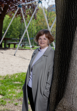 Ann Dale leaning against a tree in front of a swing set